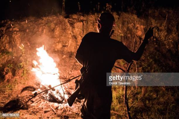 A guerillas of the New People's Army keeps a fire burning to keep warm on April 1 2017 in the remote hinterlands of Mountain Province Philippines The...