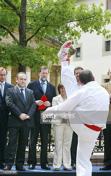 Spain's opposition Popular Party leader Mariano Rajoy watches a traditional dance with Vizcaya Provincial Government candidate Carlos Olazabal during...