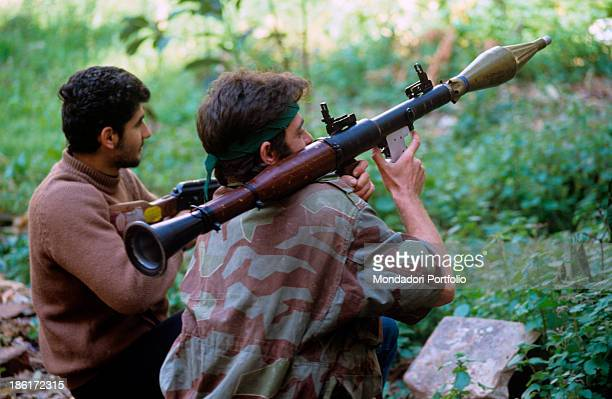 Guerrilla fighters armed with rifle and rocket launcher kneeling and guarding the horizon Italian US and French troops recently left the Lebanese...