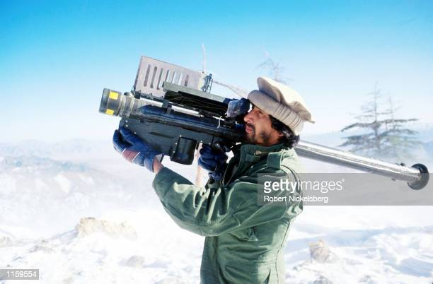 A guerrilla soldier aims a stinger missle at passing aircraft near a remote rebel base in the Safed Koh Mountains February 10 1988 in Afghanistan The...