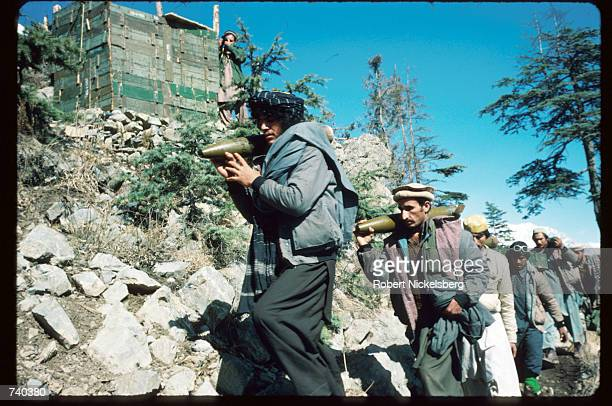 Guerrilla soldiers carry BM12 shells to the front from a remote base in the Safed Koh Mountains February 10 1988 in Afghanistan A Sovietsupported...