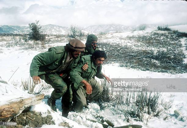 Guerrilla soldiers help a wounded man back to a remote base in the Safed Koh mountains February 10 1988 in Afghanistan The end of Soviet military...