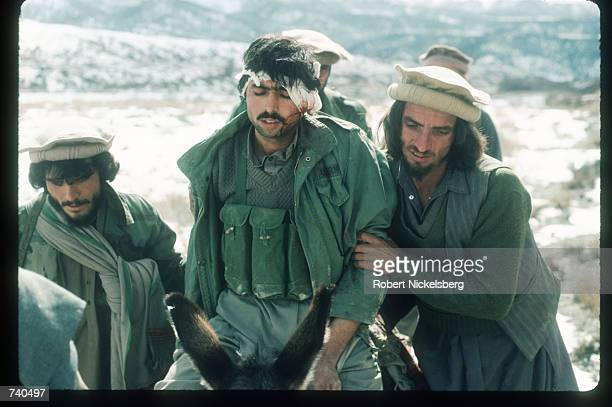 Guerrilla soldiers help a wounded man back to a remote base in the Safed Koh mountains February 10 1988 in Afghanistan A Sovietsupported communist...