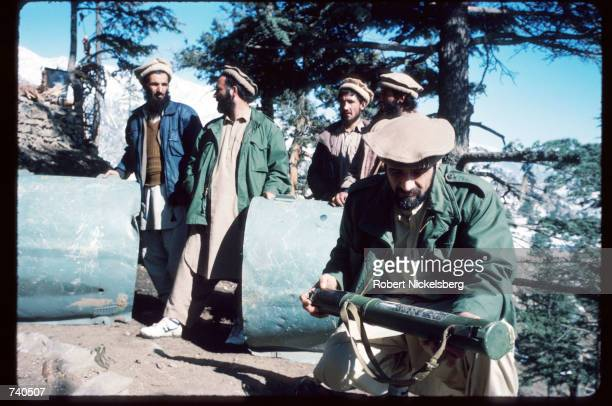 Guerrilla soldiers pose with debris from a Russian jet they shot down at a remote base in the Safed Koh Mountains February 10 1988 in Afghanistan A...