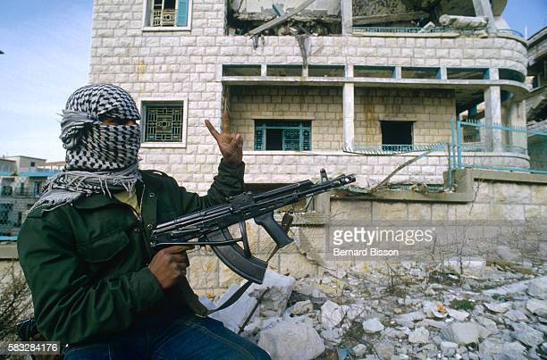 Guerrilla with the Popular Front for the Liberation of Palestine stands beside a ruined building in Beirut, wearing a kaffiyeh over his head, holding...