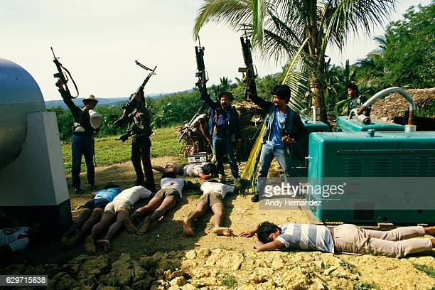 Guerrillas from the New People's Army standing behind dead bodies