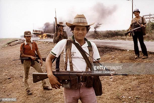 Guerrillas in El Salvador stand before a buring truck used as a roadblock