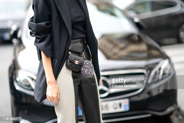 A guest a black jacket black and white leather pants a black Chanel beltbag a grey tweed Chanel coin purse outside Ralph Russo during Paris Fashion...