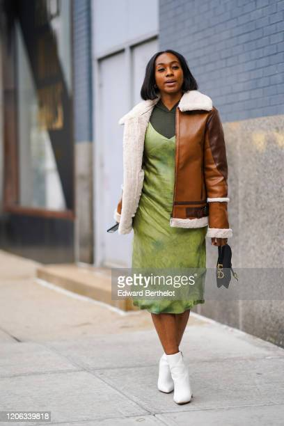 A guest a brown leather aviator jacket with white wool inner lining a green dress white pointy boots a Dior bag during New York Fashion Week Fall...