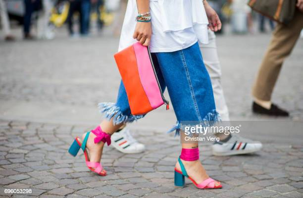 A guest a striped clutch orange and pink is seen during Pitti Immagine Uomo 92 at Fortezza Da Basso on June 14 2017 in Florence Italy