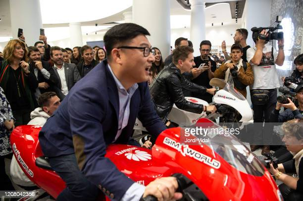 Guest and Jorge Lorenzo ride motorbike simulators during the inauguration of Espai Huawei Flagship Barcelona at Plaça Catalunya on February 22, 2020...