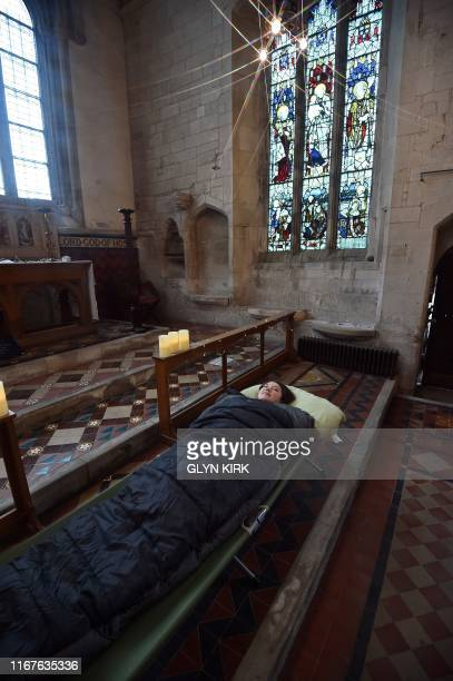 Guest Andrea Stewart tries out her bed before nightfall at St Mary's Church, where guests can pay to stay overnight in what is known as 'champing',...