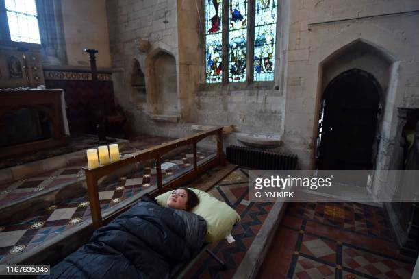 Guest Andrea Stewart tries out her bed before nightfall at St Mary's Church where guests can pay to stay overnight in what is known as 'champing' in...