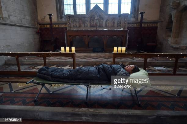 TOPSHOT Guest Andrea Stewart tries out her bed before nightfall at St Mary's Church where guests can pay to stay overnight in what is known as...