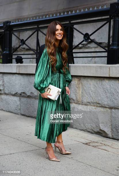 Guest arrives at the Marc Jacobs show during New York Fashion Week wearing a green dress and white handbag on September 11, 2019 in New York City.