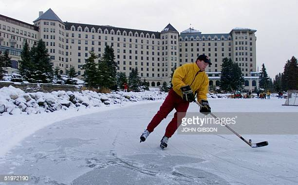 A guest at the Chateau Lake Louise plays hockey on the frozen Lake Louise 25 November 2000 The Hotel is the second oldest in Banff National Park