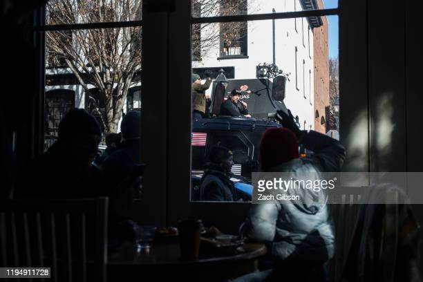 A guest at Urban Farmhouse Coffee Shop waves as InfoWars host Alex Jones drives past in an armored vehicle during a rally organized by The Virginia...