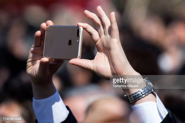 Guest attendee uses an Apple Inc. IPhone to take a photograph of Japan's Prime Minister Shinzo Abe during the cherry blossom viewing party at the...