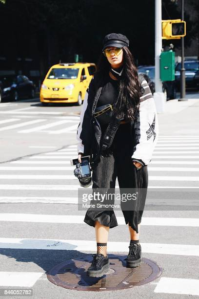 Guest attending New York Fashion Week wearing black and white oversized bomber jacket black cap and black coulottes at the Skylight Clarkson on...