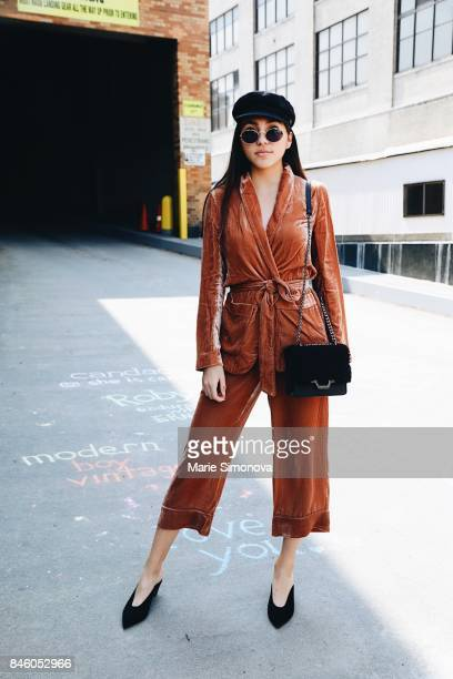Guest attending New York Fashion Week wearing black sunglasses velvet suit black cap and bag at the Skylight Clarkson on September 11 2017 in New...