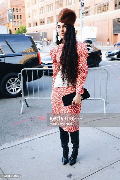 A guest attends a runway show wearing red and white polka dot dress fur cap and black leather shoes on September 11 2017 in New York City