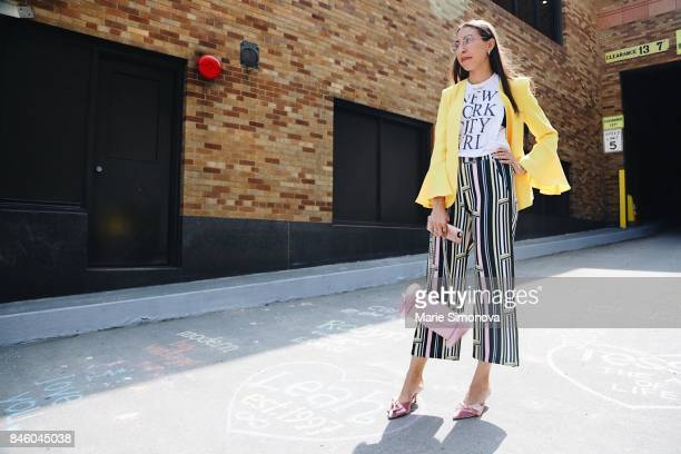 A guest attends New York Fashion Week wearing yellow jacket printed Tshirt colorful pants with stripes and light pink bag and shoes at the Skylight...