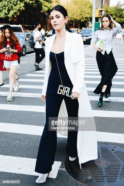 A guest attends runway show wearing white coat black dress and printed bag during New York Fashion Week on September 11 2017 in New York City