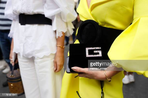 Guest, bag details, wearing Givenchy clutch outside Giambattista Valli during Paris Fashion Week Womenswear Spring Summer 2020 on September 30, 2019...