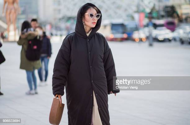 A guest black hooded coat is seen at the Hera Seoul Fashion Week 2018 F/W at Dongdaemun Design Plaza on March 22 2018 in Seoul South Korea