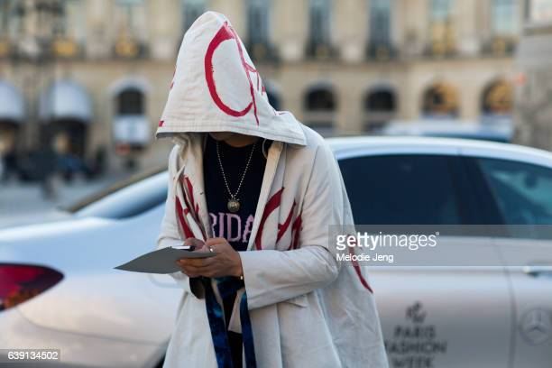 A guest checks her phone and wears a white hooded top with text and an Alberta Ferretti 'Friday' sweater outside the Balenciaga show at Place Vendome...