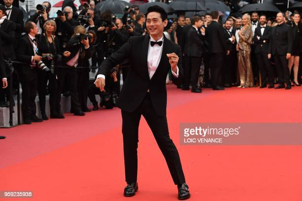 A guest dances on the red carpet as he arrives on May 16 2018 for the screening of the film 'Burning' at the 71st edition of the Cannes Film Festival...