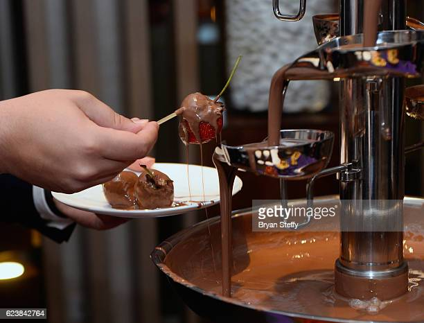 A guest dips a strawberry in a chocolate fountain during the Roc Nation Latin Grammy Midnight Brunch at the Nobu Hotel Caesars Palace on November 16...