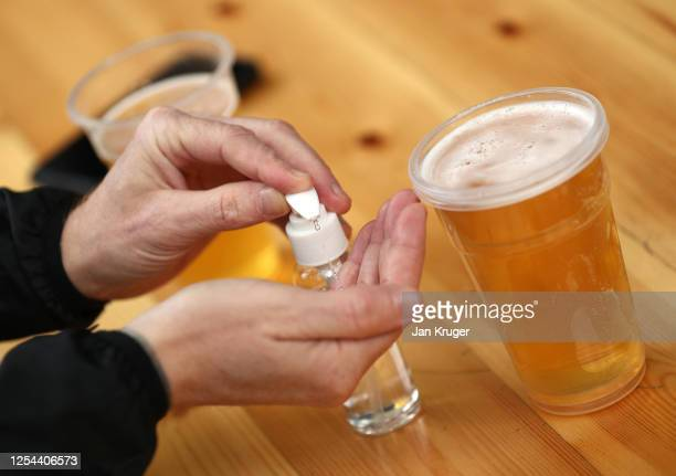 Guest disinfects his hands at a pub, as relaxed lockdown restrictions allow this for the first time since March, as Liverpool play their first home...