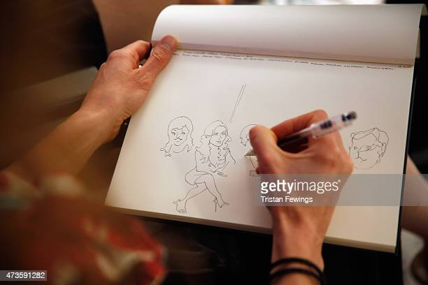 A guest draws a cartoon while watching the Variety and UN Women's panel discussion on gender equality at 68th Cannes Film Festival at Radisson Blu on...