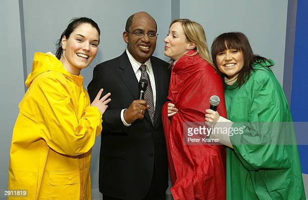 Guest dressed as weather forecasters pose with the Do The Weather With Al experience wax figure at Madame Tussauds New York January 29 2004 in New...