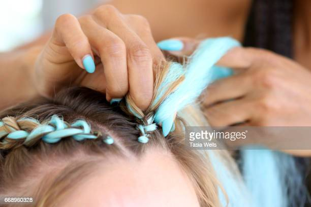 Guest gets hair braided at 40z and Waffles x Coachella Party on April 15 2017 in Palm Springs California
