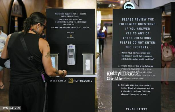 A guest gets hand sanitizer at a kiosk that also dispenses complimentary masks and gloves at an entrance to Mandalay Bay Resort and Casino after the...