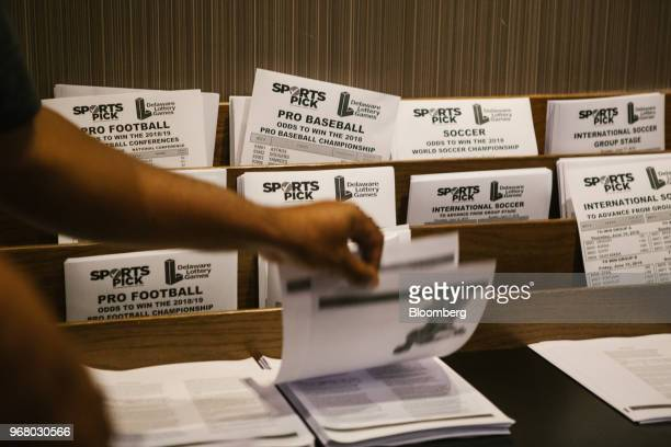 A guest grabs pick sheets during the launch of fullscale sports betting at Dover Downs Hotel and Casino in Dover Delaware US on Tuesday June 5 2018...