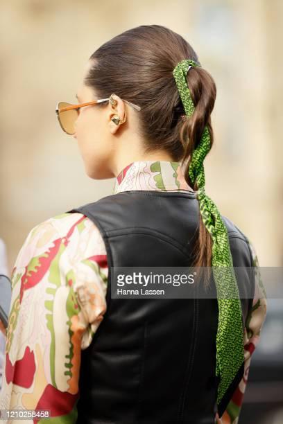 Guest, hair detail, wearing Miu Miu green scarf headpiece, printed blouse, leather jumpsuit and peach clutch outside the Miu Miu show during Paris...