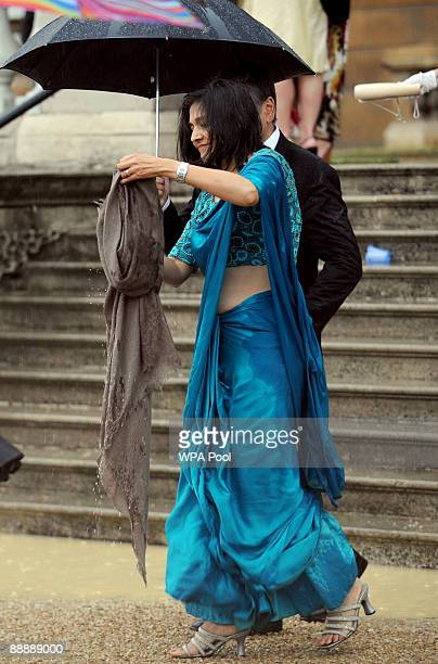 A guest heads for cover as heavy rain begins to fall during the first Royal Garden Party of the summer at Buckingham Palace on July 7 2009 in London...