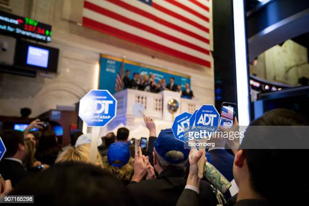 Guest hold signs as the ADT Inc executives ring the opening bell during the company's initial public offering on the floor of the New York Stock...