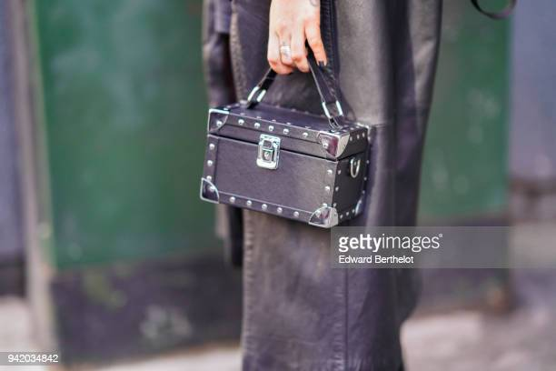 A guest holds a black rectangular rigid bag box during London Fashion Week February 2018 on February 16 2018 in London England