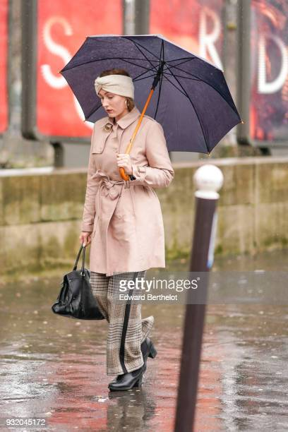A guest holds a black umbrella and wears a beige turban a peach trenchcoat a black shopping bag light brown princeofwales checkered pants with a...