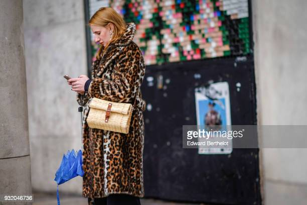 A guest holds a blue umbrella wears a leopard pattern coat a straw handbag during Paris Fashion Week Womenswear Fall/Winter 2018/2019 on March 4 2018...