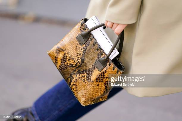 A guest holds a brown snake print leather bag outside Haider Ackermann during Paris Fashion Week Womenswear Spring/Summer 2019 on September 29 2018...