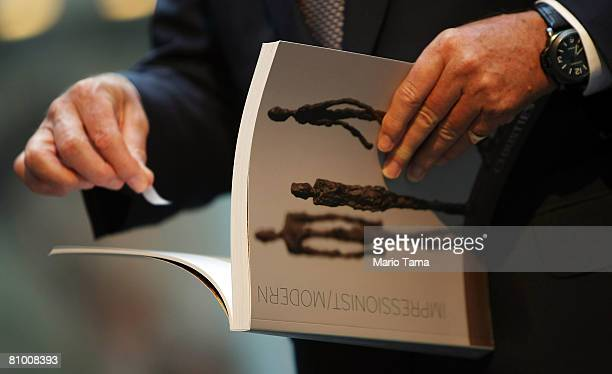 A guest holds a catalog before entering Christie's New York Impressionist and Modern Art Evening Sale May 6 2008 in New York City The sale featured...