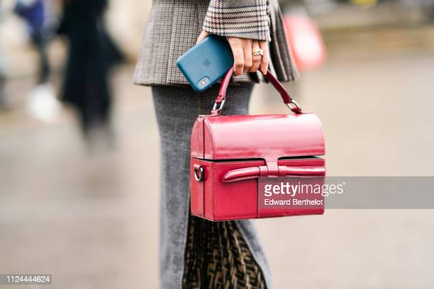 A guest holds a red bag and an iphone outside Elie Saab during Paris Fashion Week Haute Couture Spring Summer 2020 on January 23 2019 in Paris France
