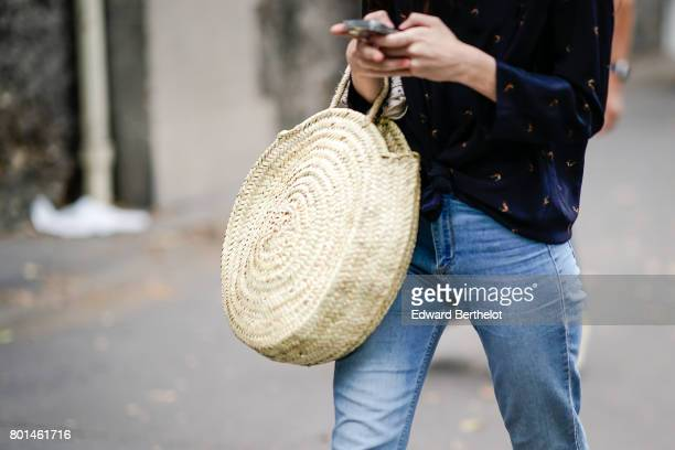 A guest holds a straw circular bag outside the Paul Smith show during Paris Fashion Week Menswear Spring/Summer 2018 on June 25 2017 in Paris France