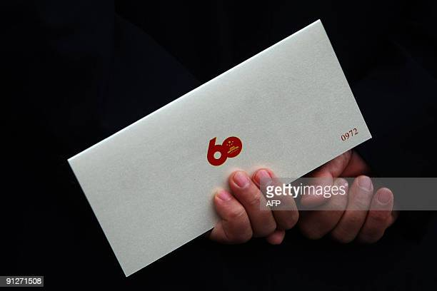 Guest holds an invitation card to attend an official banquet on the eve of the 60th anniversary of the founding of the People's Republic of China on...