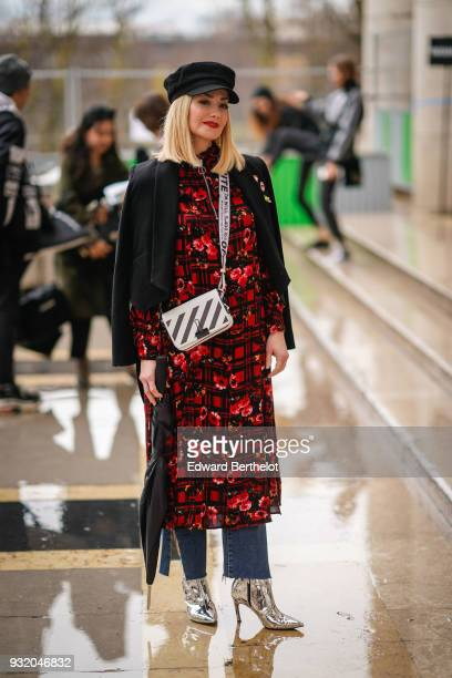 A guest holds an umbrella and wears a black cap a black jacket a black and red floral print dress ripped jeans silver high heels boots a black and...